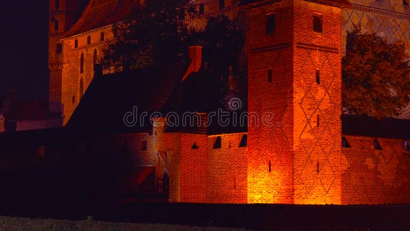 A beautiful shot next to an old castle at night with a glowing light _ in a traditional place _ in the pogrom of Poland 1-2019.  stock photos