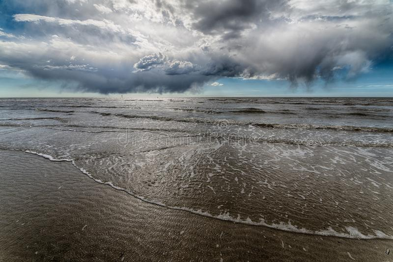 Beautiful shot of the ocean shore with the dark clouds of the sky hanging above stock photo