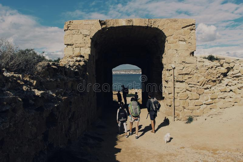 Beautiful shot of people walking through a small brick tunnel near the sea with a cloudy sky stock image