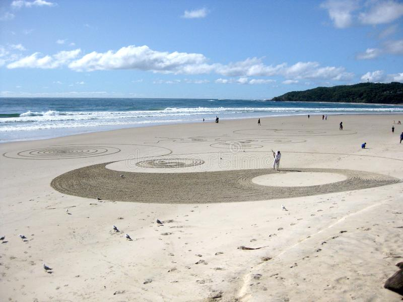 Beautiful shot of a person drawing yin and yang on the sandy surface near the water royalty free stock images
