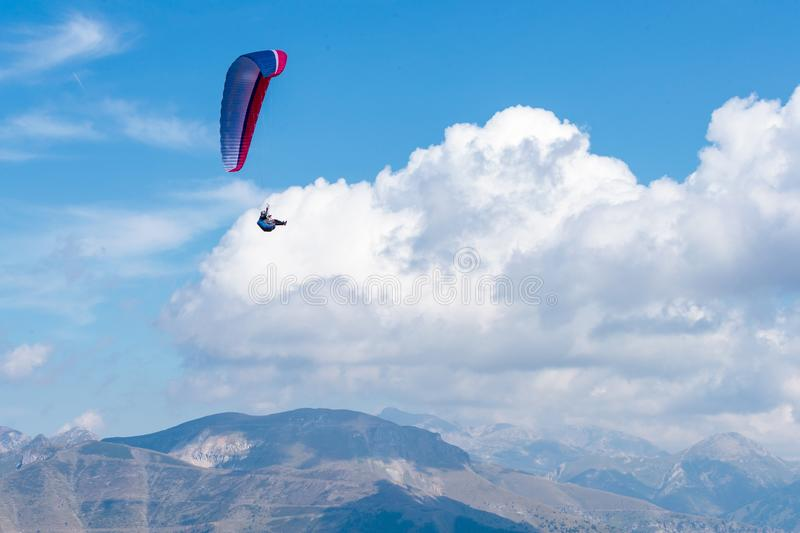 Beautiful shot of a person paragliding high in the sky above the mountains - extreme concept. A beautiful shot of a person paragliding high in the sky above the royalty free stock photos