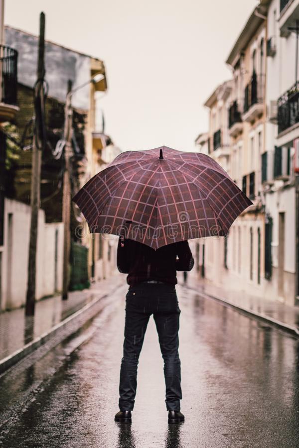 Beautiful shot of a person wearing black pants holding umbrella on a road royalty free stock photos
