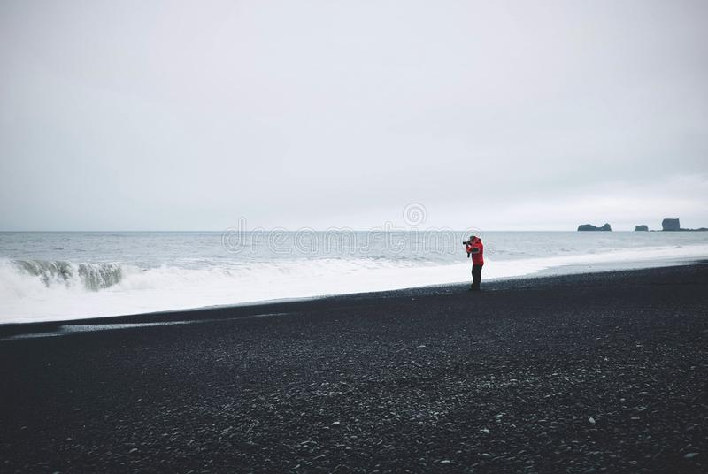 Beautiful shot of a photographer standing on the shore near the water under a cloudy sky stock photo