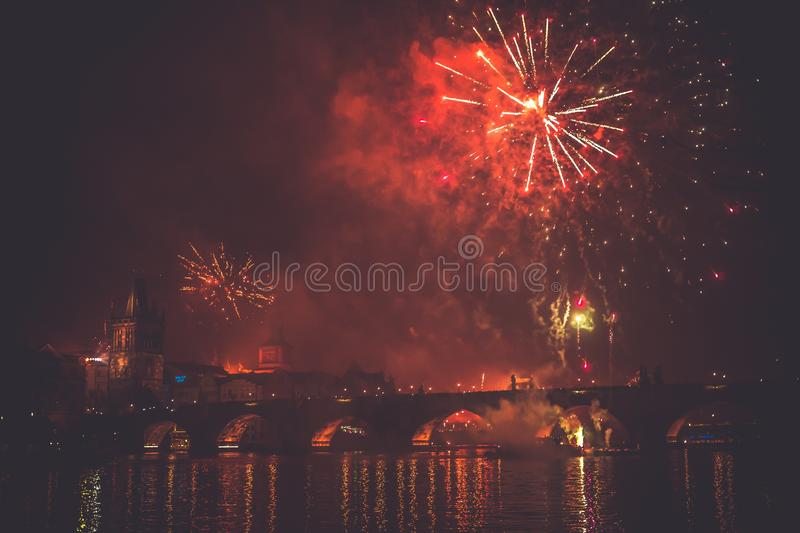 Beautiful shot of a red-colored firework in the night sky above a bridge on a river royalty free stock photography