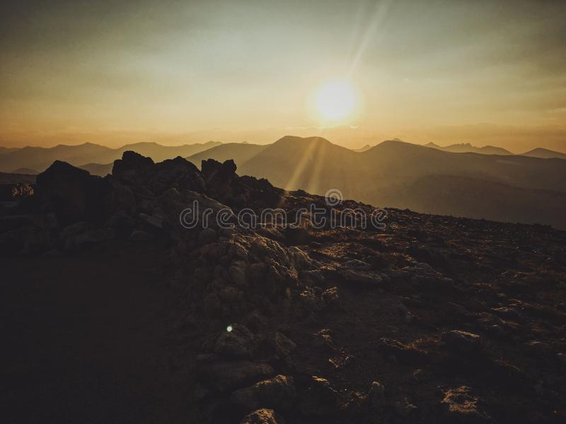 Beautiful shot of rocks on top of the mountain with the sun shining in the background royalty free stock photography