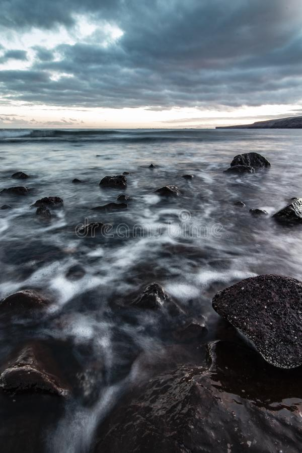 Beautiful shot of rocky coast of the sea with amazing water texture and breathtaking cloudy grey sky stock photo