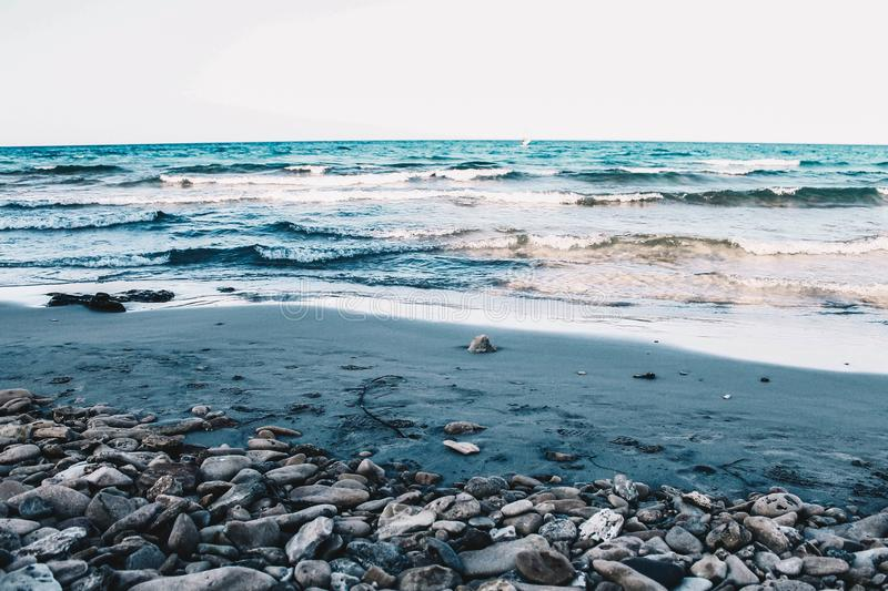 Beautiful shot of a rocky and sandy beach of the sea with medium waves under a clear blue sky stock photography