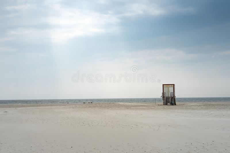 Beautiful shot of a sandy beach during a peaceful sunny day with a small wooden structure in site. A beautiful shot of a sandy beach during a peaceful sunny day royalty free stock photography