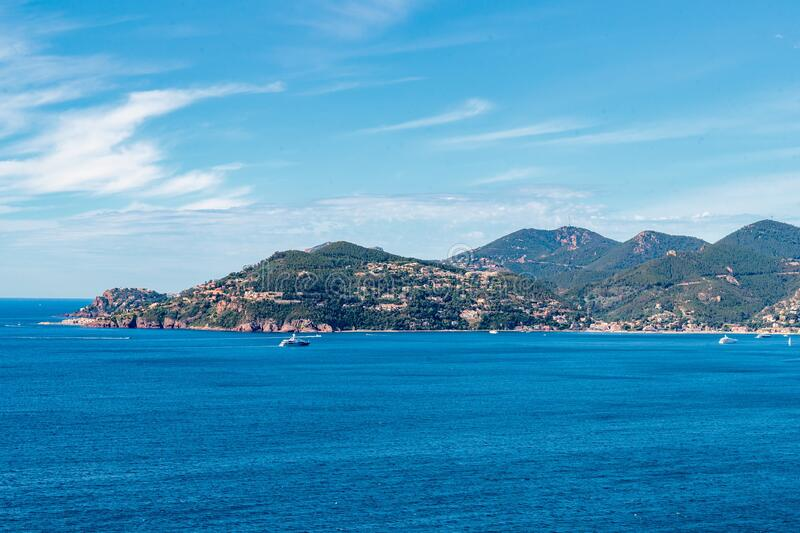 Beautiful shot of the sea with forested mountains in the distance in Theoule sur mer, France stock photo