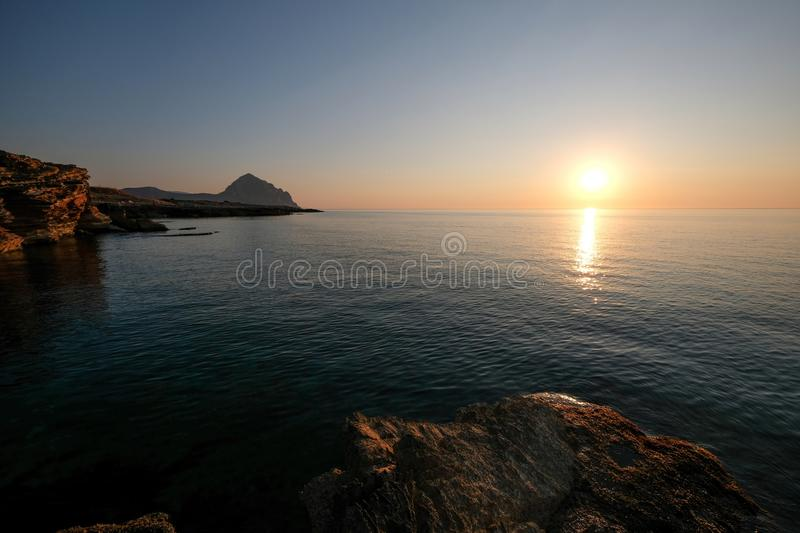 Beautiful shot of a sea near rocky cliffs with the sun in the background at sunset. A beautiful shot of a sea near rocky cliffs with the sun in the background at stock photography