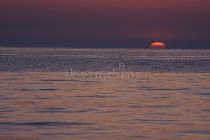 Beautiful shot of a sea with a red sun in the purple sky in the background in south Africa. A beautiful shot of a sea with a red sun in the purple sky in the royalty free stock photos
