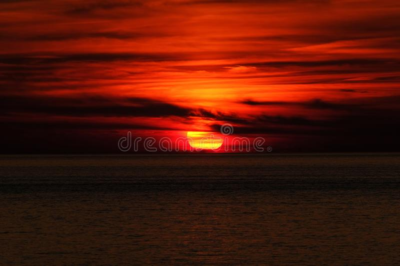 Beautiful shot of a sea and sun behind the clouds at sunset. A beautiful shot of a sea and sun behind the clouds at sunset royalty free stock photo