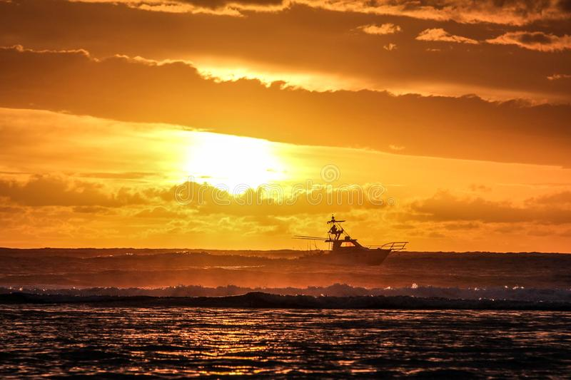 Beautiful shot of sea waves and a boat in the distance with the sun in the orange sky. A beautiful shot of sea waves and a boat in the distance with the sun in royalty free stock photos