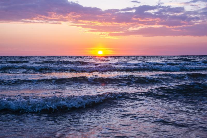 Beautiful shot of sea waves under the pink and purple sky with the sun shining during golden hour. A beautiful shot of sea waves under the pink and purple sky stock photo