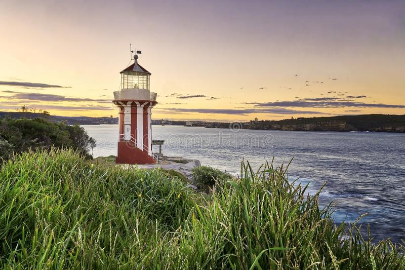 Beautiful shot of a small red and white lighthouse at the shore of the sea during sunset. A beautiful shot of a small red and white lighthouse at the shore of stock photo