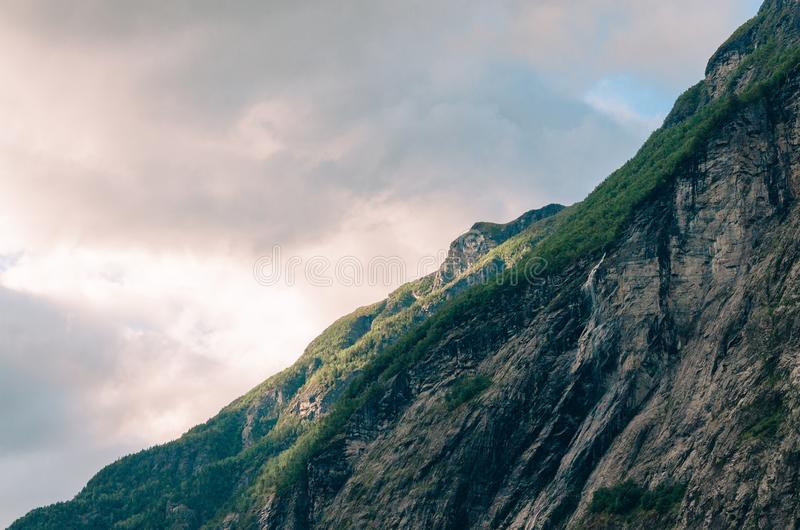 Beautiful shot of a steep cliff with greenery on it in the mountains on a cloudy day. A beautiful shot of a steep cliff with greenery on it in the mountains on a stock photo