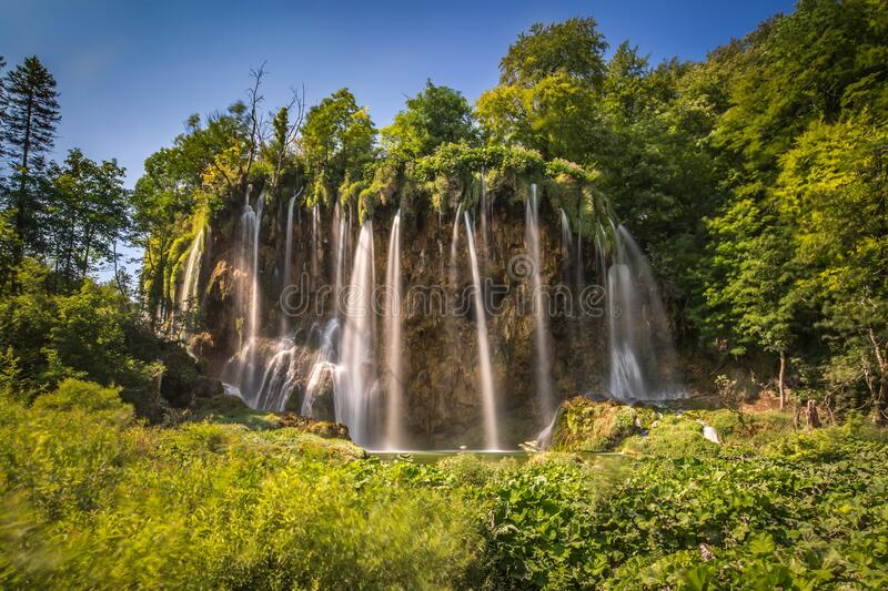Beautiful shot of waterfalls off the cliff surrounded by green trees and plants. A beautiful shot of waterfalls off the cliff surrounded by green trees and royalty free stock photos
