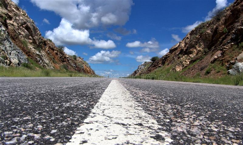 Beautiful shot of a white line on an empty road in the middle of mountains under a cloudy sky stock image