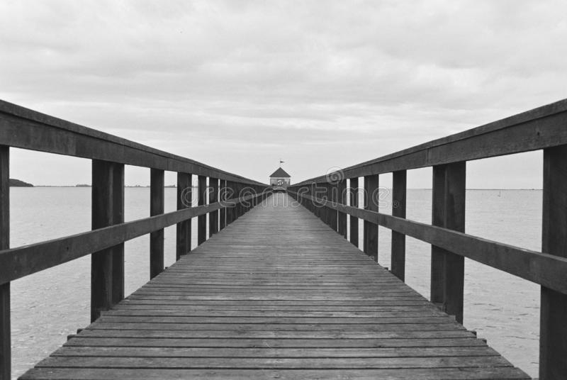 Beautiful shot of a wooden pathway over the water towards the booth in black and white. A beautiful shot of a wooden pathway over the water towards the booth in stock photo