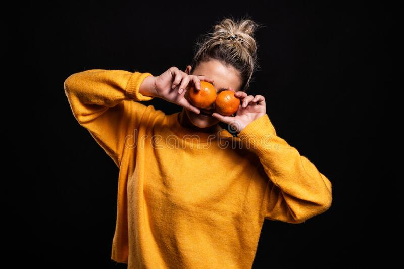 Beautiful shot of a young blonde girl in an orange sweater posing with clementine fruits royalty free stock photography