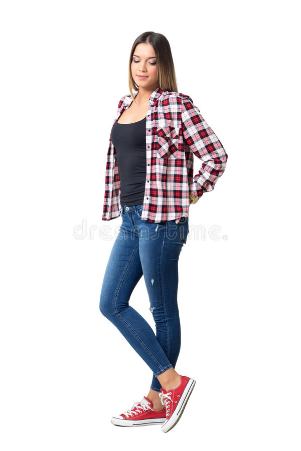 Beautiful shy casual girl wearing jeans, red and white plaid shirt and sneakers looking down. stock photos