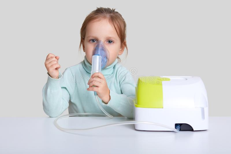 Beautiful sick girl has inhalation therapy, uses portable nebulizer, holds mask vapor, sits at white desktop, isolated over studio. Background. Respiratory stock photos