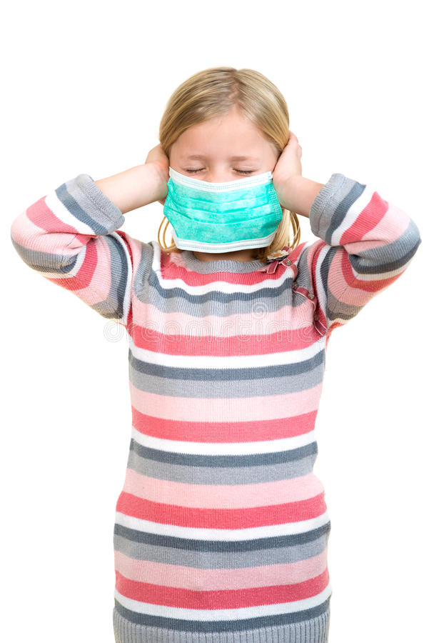Beautiful sick girl protect flu by the mask for kid. Close up image of a cute kid with respiratory problem or flu. Adorable little sick girl with medical mask royalty free stock photo