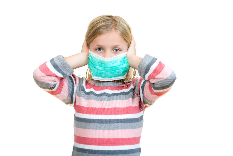 Beautiful sick girl protect flu by the mask for kid. Close up image of a cute kid with respiratory problem or flu. Adorable little sick girl with medical mask royalty free stock images