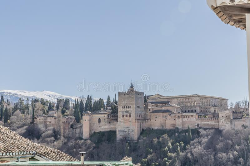 Beautiful side view of the Alhambra on a hill with arid terrain and some green trees with a snowy mountain in the background. A wonderful sunny day with a blue royalty free stock photos