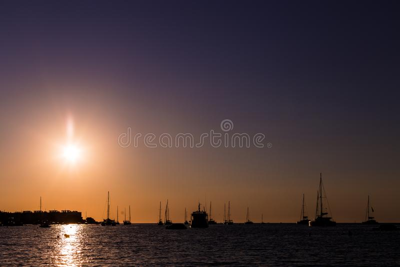 Beautiful silhouette of the boats in the port at sunset in Ibiza. Holidays and summer concept. Sailboat, sunrise, mast, mediterranean, dock, anchor, float stock photography