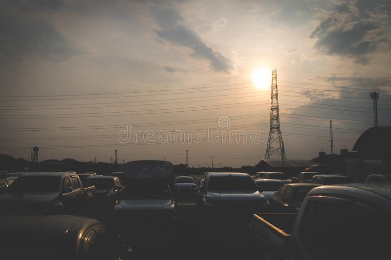 A beautiful silhouette image of many cars parked in an outdoor parking lot, with the backdrop of the sky in the evening. At Ayutthaya, Thailand royalty free stock photo