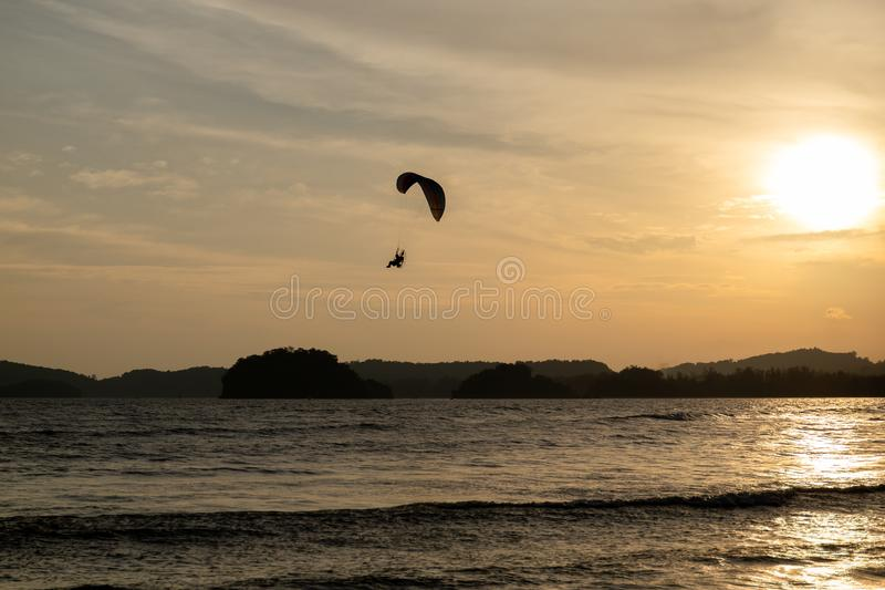 Beautiful Silhouette of paraglider flying in the sky of sunset on the beach. royalty free stock photos