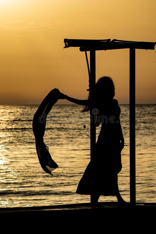 Beautiful silhouette at sunset golden sea water. Beautiful female silhouette of unrecognizable slim tall woman with silk scarf at sunset in front of golden stock photos