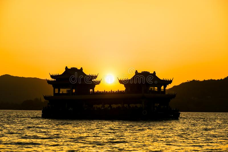 The beautiful of silhouette sunset landscape scenery of Xihu West Lake, Sightseeing boat and pavilion in Hangzhou CHINA stock photo