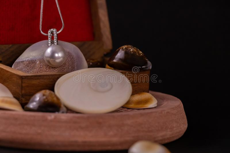 Beautiful Silver Necklace with Pearl Pendant on wooden box and spreaded seashells on dark background stock photos