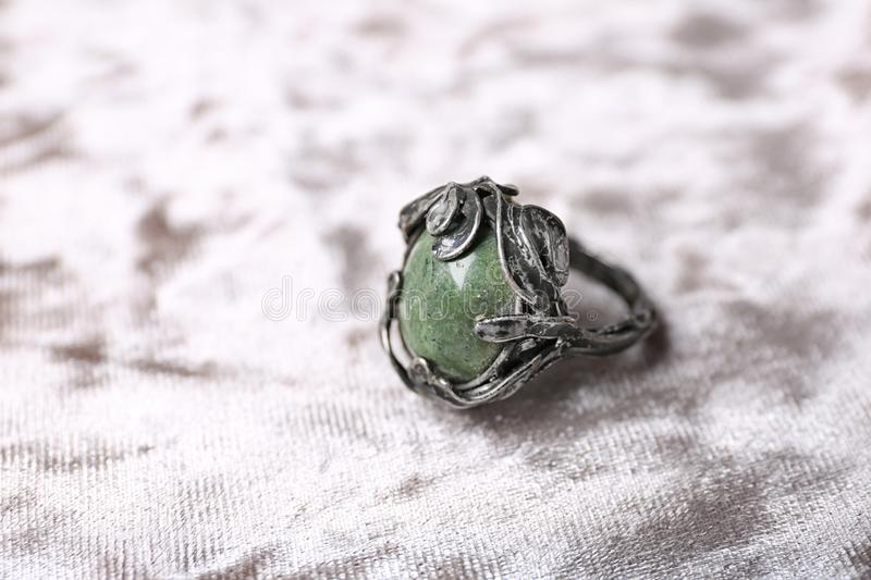 Beautiful silver ring with opal gemstone on fabric. Beautiful silver ring with opal gemstone on light fabric royalty free stock images