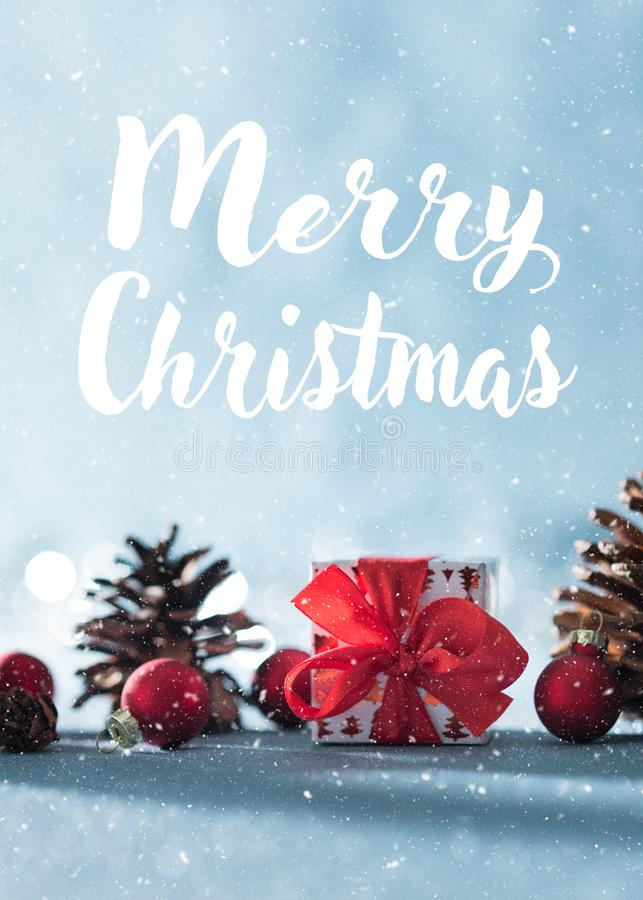 Beautiful simple Christmas background with copy space. Cute Christmas present, red ornaments and pine cones on blue background. stock photo