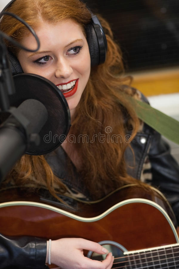 Beautiful singer recording and playing guitar stock photo