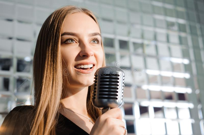 Beautiful Singing Girl. Beauty Woman with Microphone. Glamour Model Singer. Karaoke song. stock image