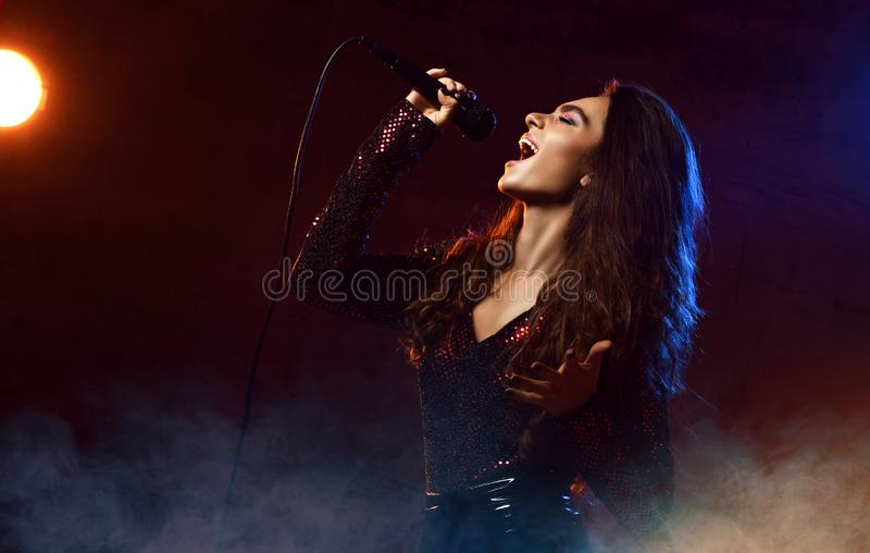 Beautiful singing girl curly afro hair. Beauty woman singer sing with microphone karaoke song on stage smoke, spotlights. Beautiful singing girl curly afro hair stock photography