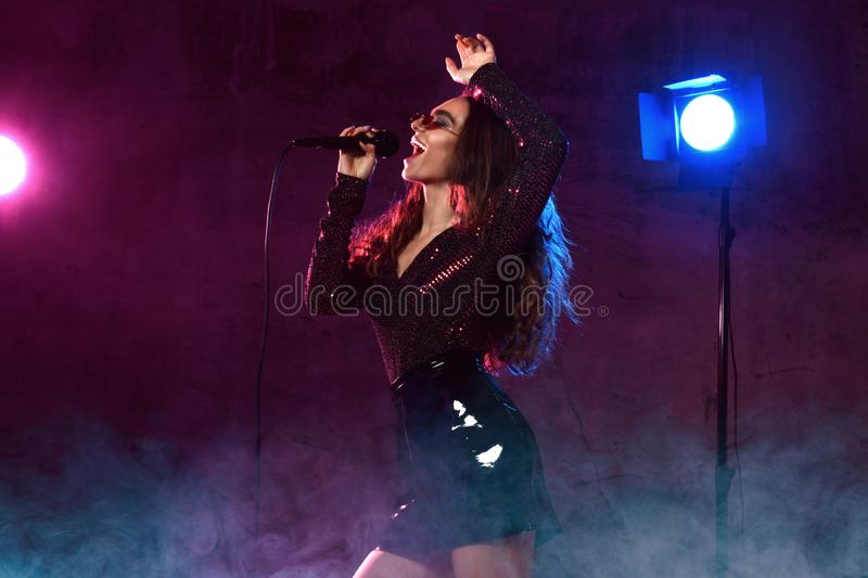 Beautiful singing girl curly afro hair. Beauty woman singer sing with microphone karaoke song on stage smoke, spotlights. Beautiful singing girl curly afro hair stock photo