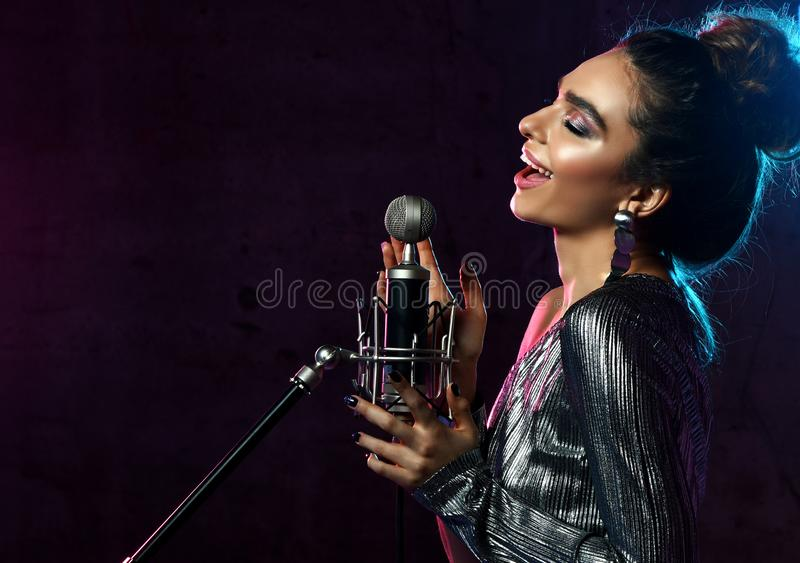 Beautiful singing girl curly afro hair. Beauty woman singer sing with microphone karaoke song on stage smoke, spotlights. Beautiful singing girl curly afro hair royalty free stock photo