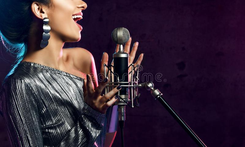 Beautiful singing girl curly afro hair. Beauty woman singer sing with microphone karaoke song on stage smoke, spotlights. Beautiful singing girl curly afro hair royalty free stock images