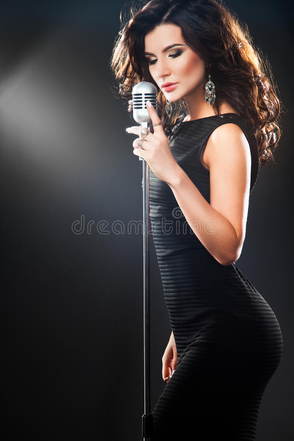 Beautiful Singing Girl in karaoke. Beauty Woman with retro Microphone stock image