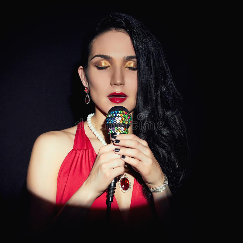Beautiful Singing Girl.Woman with Microphone royalty free stock image