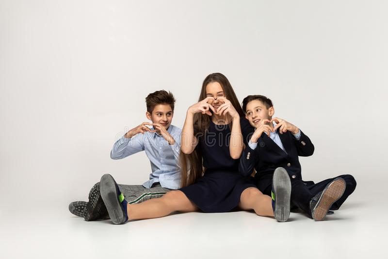 Beautiful sister sitting on the ground with two younger brothers stock photography