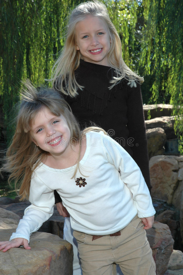 Beautiful Sisters. Two beautiful little blond sisters play and explore a nature area in a park. Spending time with family and being together stock image