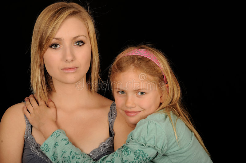 Beautiful Sisters. A portrait of two beautiful sisters, on black studio background stock photo