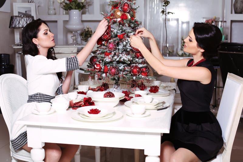 Beautiful sisters decorating Christmas tree at home stock photos