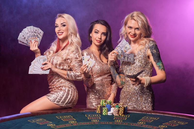 Beautiful girls with a perfect hairstyles and bright make-up are posing standing at a gambling table. Casino, poker. royalty free stock photos